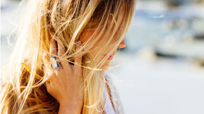 Haarpflege: Nahaufnahme einer Blondine, die draußen ist. Ihr weht Wind durchs Haar.uch die Haare eine gute Pflege.