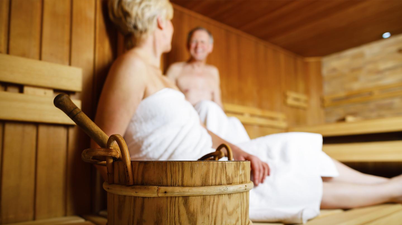 Richtig saunieren: Älteres Ehepaar in weiße Handtücher gehüllt in der Sauna.
