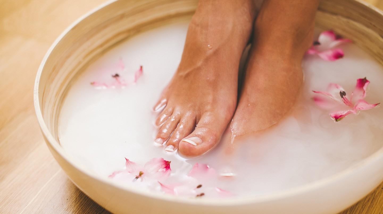 Fußpflege bei Diabetes: Füße in einer Schüssel mit Wasser in dem Blüten schwimmen.